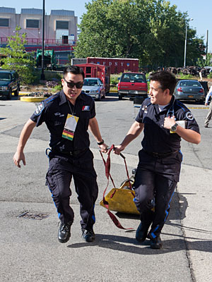 Medical students Ana Cicneros and Drew Carlton carry Samuel Alperin after a simulated bus explosion.